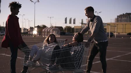 multikulturális : Multiethnic young people playing with shopping cart.s. Male friends standing near the shopping corts with their girlfriends. Young man explaining something to others. Outdoors on parking zone Stock mozgókép