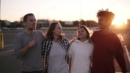 quatro : Group of mixed race friends walking embracing and talking together in city. They are two girls and two boys in their twenties, friendship and lifestyle concepts, autumn clothing. Sun strongly shining on the background. Front view Vídeos