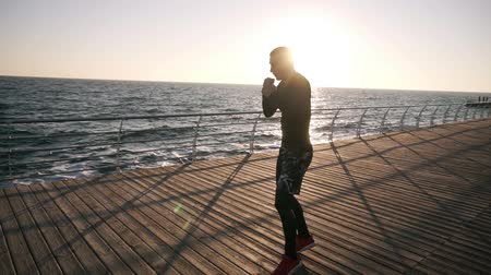 fegyelem : Male boxer fighter training punches outdoors, workout with invisible opponent. Healthy lifestyle and energy with motivation - concept of strength training near the sea. Morning sun shines on the background