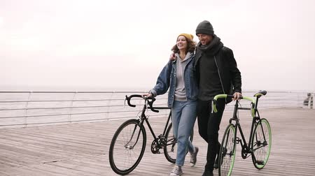 clothes line : Modern young hipster couple walking together with their bikes near the sea at autumn day embracing. Walking by wooden deck in daytime, smiling and talking. Slow motion Stock Footage