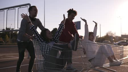 quatro : Side view of a young friends having fun outdoors on shopping trolleys. Multiethnic young people racing on shopping carts on the parking zone with their girlfriends. Couple laughing, having time together. Sun shines on the background