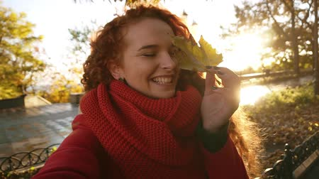 positividade : Beautiful young woman with long curly hair closed eye with autumn leaf. Girl smiling at camera and posing. Outdoor. Holidays. Autumn. Sun shines on the background