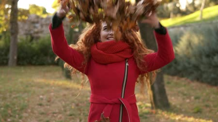 autumns : Portrait of a happy red head woman throwing leaves around and looking up on an autumns day. Autumn leaves falling on happy young woman in city park and she is whirling around in enjoyment. Smiling girl in red coat in park. Front view