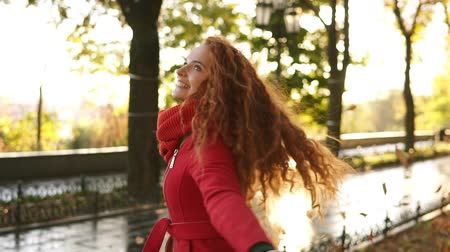autumns : Happy, smiling girl throwing leaves around on an autumns day. Autumn leaves falling on happy young woman in city park and she is whirling around in enjoyment. Smiling girl in red coat in park. Slow motion
