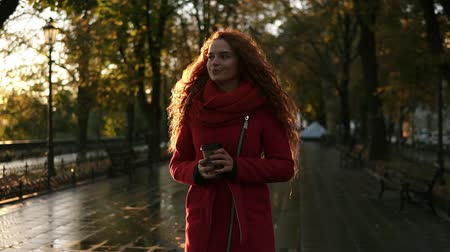 ona : Red haired stunning woman walking on a city park. Cold weather, she wears red colored coat. Long haired beautiful, smiling girl drinks coffee from to go cup. Lens flares, golden sunlight. Front view Dostupné videozáznamy