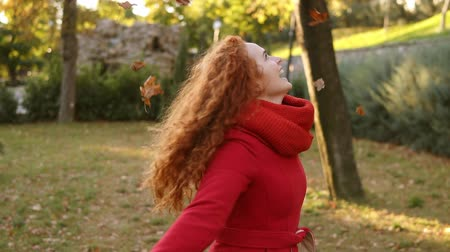 autumns : Portrait of a happy red head woman throwing leaves around and looking up on an autumns day. Autumn leaves falling on happy young woman in city park and she is whirling around in enjoyment. Smiling girl in red coat in park. Front view. Slow motion