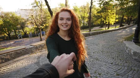 vlasy : Young attractive girl in dark knitted sweater joyfully walking in a colorful autumn city park on pavement. Red curly haired girl enjoying autumn foliage, turns around joyfully smiling at camera, leading her boyfriend with hand