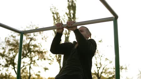 posição : Strong athlete in black sportclothes doing pull-up on horizontal bar. Sun shines on the background and trees around him. Slow motion