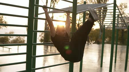 lift ups : Caucasian fit man workout out on horizontal bars outdoors . Young man training abnominal muscules doing push ups outdoors during the morning sunrise
