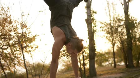 handstand : Young handsome man performing handstand on parallel bars outdoors. Beautiful head down position, perfect balance. Morning, trees on the background