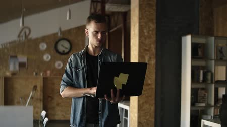 public worker : Attractive concentrated young business man is walking with a laptop in his hand and typing. Caucasian man working in public workplace with brick wall interior. Slow motion Stock Footage