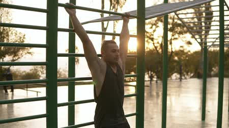 horizontal bar : Strong fit man workout out on horizontal bars outdoors . Young man training abnominal muscules lifting legs high to the head doing push ups outdoors during the morning sunrise Stock Footage