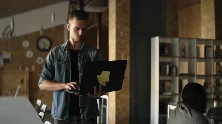 gençlik kültürü : Attractive concentrated young business man is walking with black laptop in his hand and typing. Caucasian man working in public workplace with brick wall interior. Slow motion. Front view