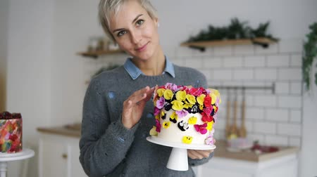 self made : Beautiful, cheerful woman in grey sweater holding self decorated cake with flowers in white modern kitchen studio. Shorthair female chef made a wedding or birthday cake with fresh, eatable flowers. Front view. Slow motion