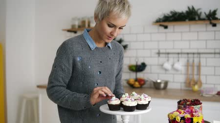 self made : Female confectioner in her kitchen with self made muffins and cakes. Fancy decorated pastry on table. Slow motion