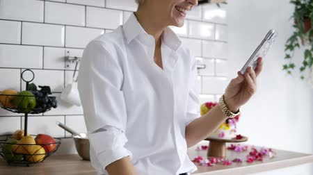 culinária : Cheerful, positive woman in white shirt standing on her white modern kitchen with smartphone in her hands, having fun, laughing. Confectioner decorated the cakes with flowers