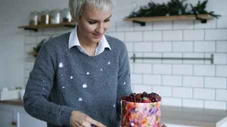 šlehačka : Grey haired woman cuts off with a knife a small piece from a beautiful cake, the dessert is decorated with berries on top, she puts it on a plate. Modern, white kitchen