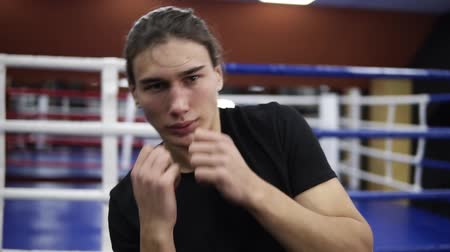 flexibility : Handhelded footage of a male boxer warming up. Twisting his body,waving hands, holding hands before face. Training process. Boxing gym