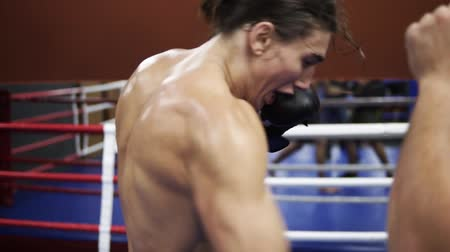 treinador : A close-up of a young european-looking man in black sports shorts with a nake torso and in boxing gloves trains in the ring with his coach, fulfills blows toprotected torso. The concept of sport, men, boxing