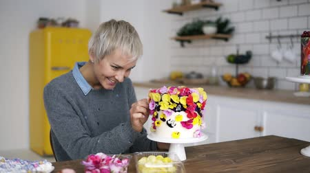 konfekció : Smiling woman in grey sweater decorates cake with flowers on white modern kitchen studio. Shorthair female chef makes a wedding or birthday cake with fresh, eatable flowers, choosing best flowers for cake