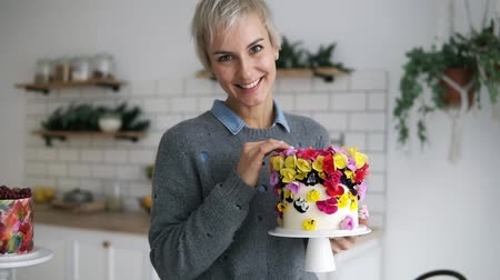 self made : Beautiful, cheerful woman in grey sweater holding self decorated cake with flowers in white modern kitchen studio. Shorthair female chef made a wedding or birthday cake with fresh, eatable flowers. Front view
