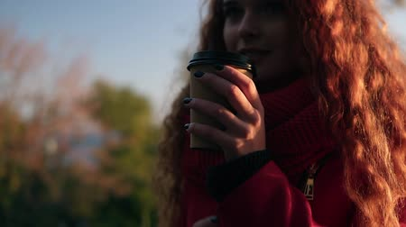 andar : Cheerful stylish young woman in red coat scarf standing outdoors on the street drinking coffee in sunshine light in autumn park. Smiling girl enjoying her day out. Overview footage