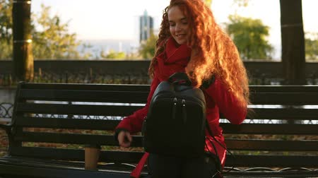 roman : Woman walking by city park with coffee togo and bag. Curly haired lady starting to read a book on a park bench, leisure time in autumn park. Lovely red haired woman in red coat sitting on a bench and relaxing