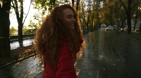 kıvırcık saçlar : Young caucasian woman walking in a colorful autumn park by wet alley, enjoying autumn foliage, turns around joyfully smiling at camera. In movement, slow motion. Trakking footage Stok Video