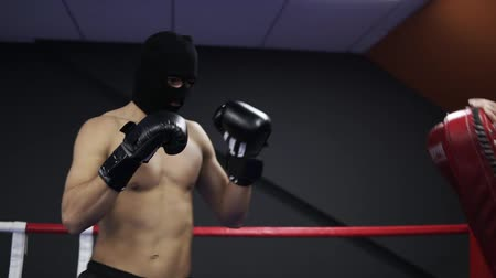 agresif : Aggressive boxer works with boxing paws with his coach in the ring. Practicing a series of leg punches. Shirtless athlete in black boxing gloves and thief mask Stok Video