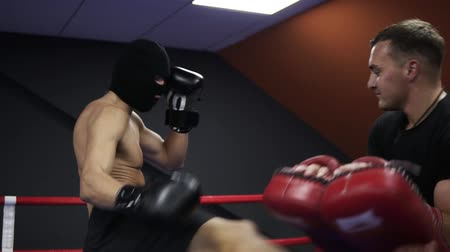 átlyukasztás : Aggressive boxer works with boxing paws with his coach in the ring. Practicing a series of leg punches. Shirtless athlete in black boxing gloves and thief mask. Slow motion