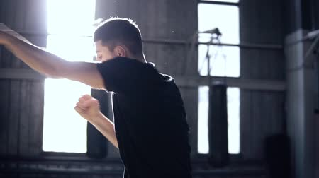 actively : Young boxer actively fulfills punches while walking back and forth. Shadowboxing in old style gym. Confident male boxer doing his training. Slow motion. Sun flares from the windows. Low angle side view footage Stock Footage