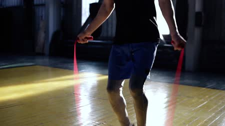 corda : Cropped footage of a male boxer in blue shorts and leggings exercising in old style gym. Close up of man training with skipping rope, highly lifting knees