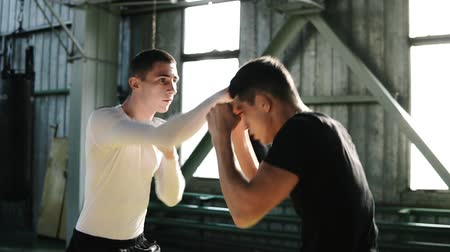 félénk : Two caucasian boxers are training, a punch to the face, a technique of striking, a stand, protection and endurance. Shy away from blows protecting the face. Boxing training together