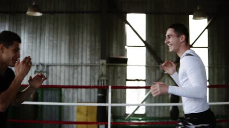 agresif : The young boxer reflects the attacks of his opponent on the boxing ring in gym They playfully attacks each other without gloves. The concept of boxing, ring, training