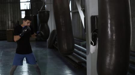 軽量 : Two male boxers in casual clothes are beating the black boxing pear. Hardworking, training process at boxing gym 動画素材