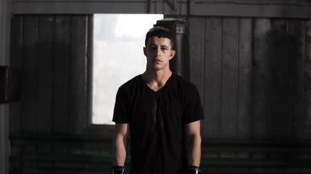 бокс : Portrait of a dark haired caucasian male boxer standing in an old fashioned boxing gym near the sand bag. Wearing casual clothes and black gloves. Sweaty and exhausted after training