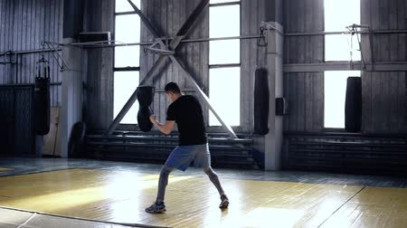 javul : Full length of a male boxer actively trainings punches while walking and moves during. Shadowboxing in old style gym. Confident male boxer doing his training. Slow motion Stock mozgókép