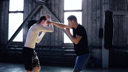 opponent : Professional two boxers are training, a punch to the face, a technique of striking, a stand, protection and endurance. The concept: love of sport, young boxers. Old style gym