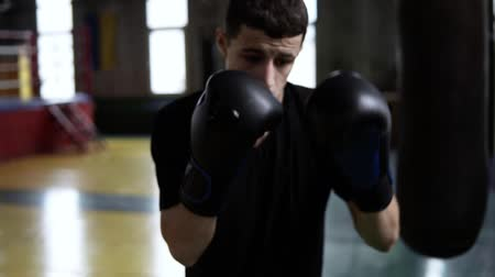 агрессивный : Determinated young boxer punching black bag in vintage stylized gym. Caucasian young man hitting the punching bag in black gloves. Close up