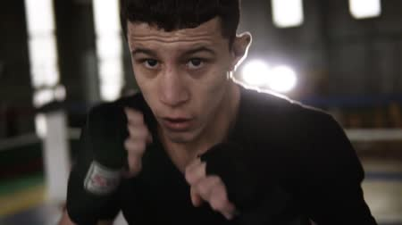 lightweight : Young man fulfills blows in black boxing bandages and looking seriously at camera in the gym. Close up tired from workout boxer. Boxing ring and gym on the background. Slow motion Stock Footage