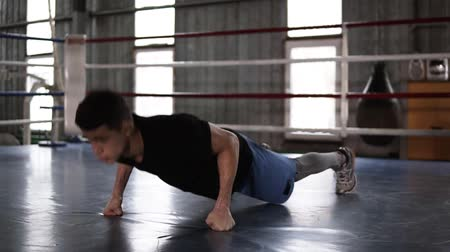 кулак : Athletic man in T shirt and shorts standing on his feet and fists and doing push-ups inside of the boxing ring. Tough power training. Slow motion