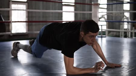 бокс : Close up of young muscular sportsman doing push-ups - from elbows to outstretched hands - while working out in boxing gym. Side view