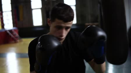 estilizado : Determinated young boxer punching black bag in vintage stylized gym. Caucasian young man hitting the punching bag in black gloves