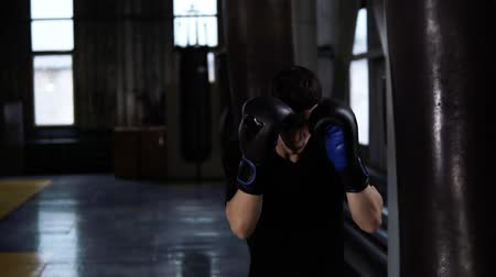 estilizado : Handsome boxer punches the heavy bag while wearing black gloves. Sport, boxing ring background. Slow motion Stock Footage