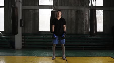 kickbox : Full length portrait of a dark haired young caucasian male boxer standing in an old fashioned boxing gym near the sand bags. Serious and tired after workout. Wearing casual clothes and black and blue gloves. Camera move away. Front view Dostupné videozáznamy