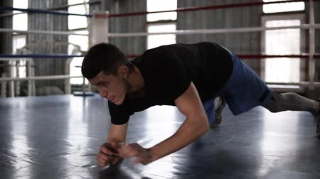 összpontosítás : Close up of young muscular sportsman doing push-ups - from elbows to outstretched hands - while working out in boxing gym Stock mozgókép