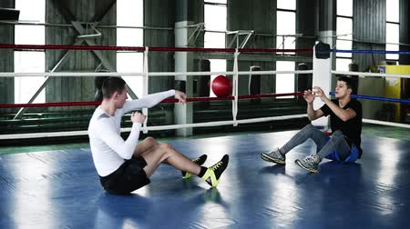 contra : Two muscular men trains in the gym together doing push-ups for abdomen and throwing heavy sportive ball during the process. Concept of: workout, boxing workout, power, hard work Stock Footage