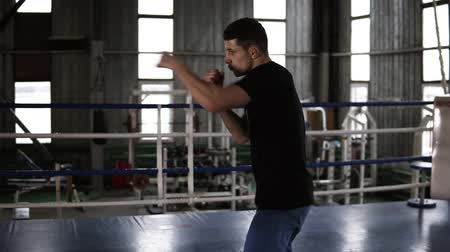 önlemek : Male athlete in black T-shirt and shirts training his punches. Moving and avoiding with shadow opponent. Guy warming up alone in gym on the boxing ring Stok Video