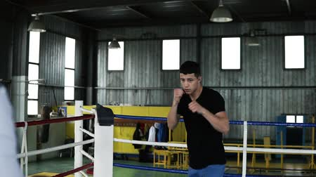 puncs : Motivated, young boxer in casual is training with coach on the ring. View from the back of the coach holding a heavy ball while guy is practicing punches and tactics steps. Old style gym on the background