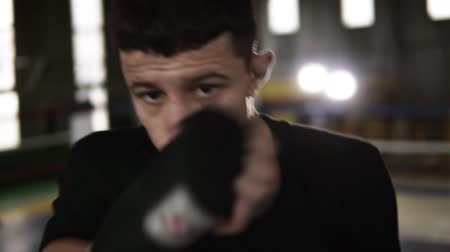 agresif : Young man in black T shirt fulfills blows in black boxing bandages and looking seriously at camera in the gym. Close up tired from workout boxer. Boxing ring, soffits and gym on the background. Slow motion